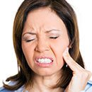 woman with toothache placing hand on her cheek